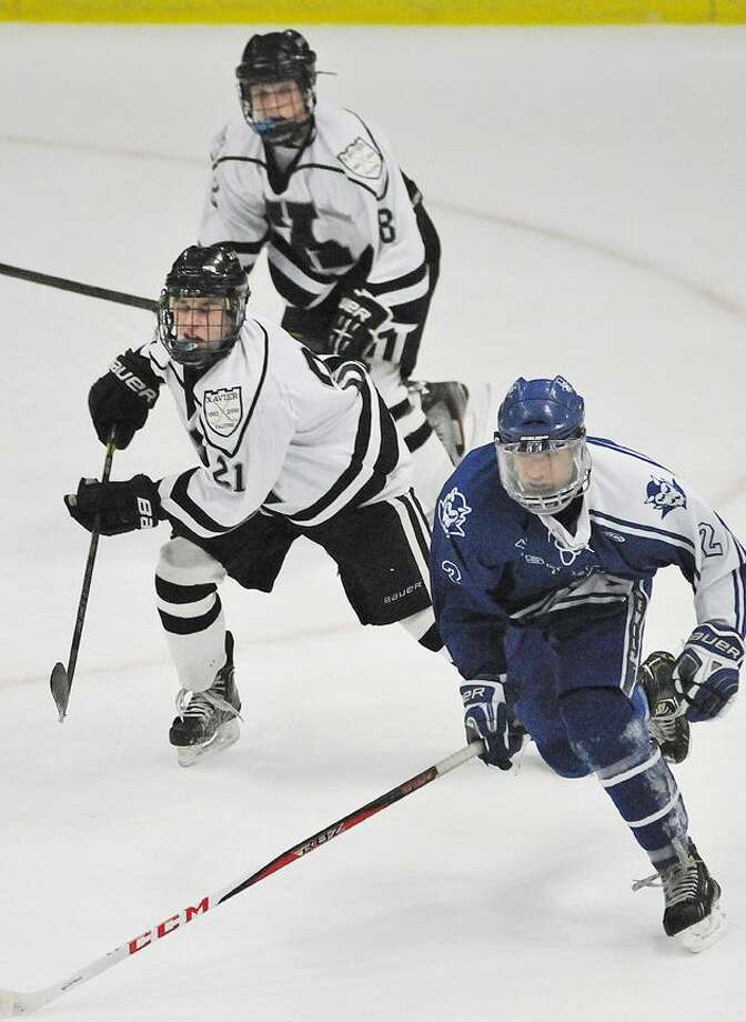 Catherine Avalone/The Middletown Press Xavier junior forward Jack Gethings (21) and freshman forward Cam Pollack (8) battle West Haven junior Jaeson Puleo for possession Wednesday night at Spurrier-Snyder Rink at Freeman Athletic Center at Wesleyan University. The Xavier Falcons (13-5-2) defeated the West Haven Blue Devils (8-11-2)  2-1 in overtime in the CIAC Division I 2013 Post Season tournament game . / TheMiddletownPress