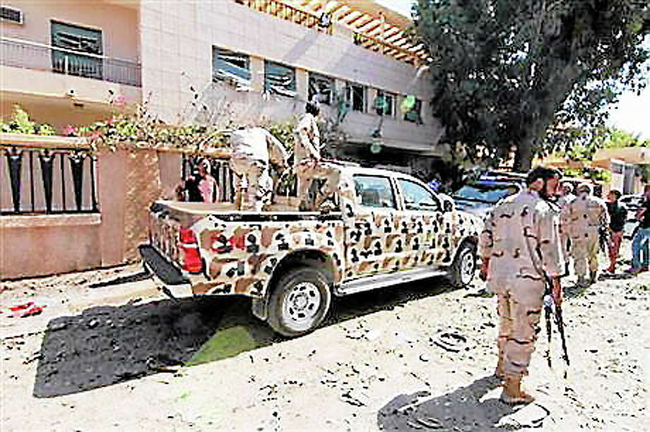 Security forces work at the site where a car bomb went off outside the building housing Swedish and Finnish consulates on Friday, Oct. 11, 2013 in Libya's eastern city of Benghazi, badly damaging the building, but leaving no casualties. Benghazi has been hit by a wave of attacks against government offices and targeted killings in recent months as security agencies struggle to secure Libya since the 2011 civil war. Weapons have proliferated and a number of militias have vied for authority, operating with impunity.(AP Photo/Mohammed el-Shaiky) Photo: Journal Register Co.