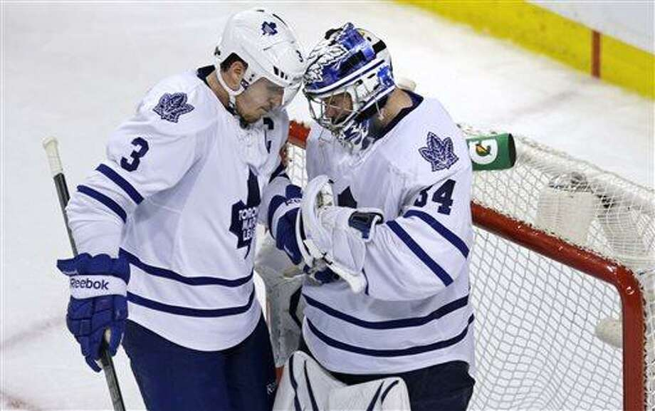 Toronto Maple Leafs goalie James Reimer, right, is congratulated by teammate Dion Phaneuf after the Maple Leafs defeated the Boston Bruins 2-1 in Game 5 of an NHL hockey Stanley Cup playoff series, in Boston on Friday, May 10, 2013. (AP Photo/Charles Krupa) Photo: AP / AP
