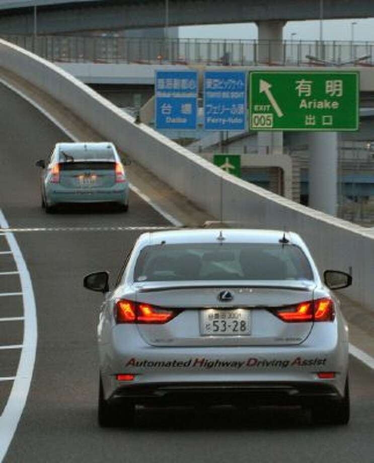 "This photo taken on October 10, 2013 shows Toyota Motor Co. demonstrating the advanced driving support system ""Automated Highway Driving Assist"" in Tokyo. The two vehicles communicate with each other, keeping in their lane and following the preceding vehicle to maintain a safety distance."