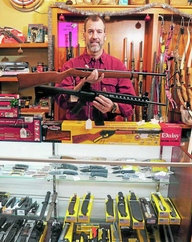 Mike Higgins, co-owner of TGS Outdoors, holds a Ruger 10/22 semiautomatic rifle, above, and a Smith & Wesson M&P 15/22 semiautomatic rifle, below, both chambered in .22 Long Rifle, Friday in Branford. Photo: Peter Hvizdak — New Haven Register       / ©Peter Hvizdak /  New Haven Register