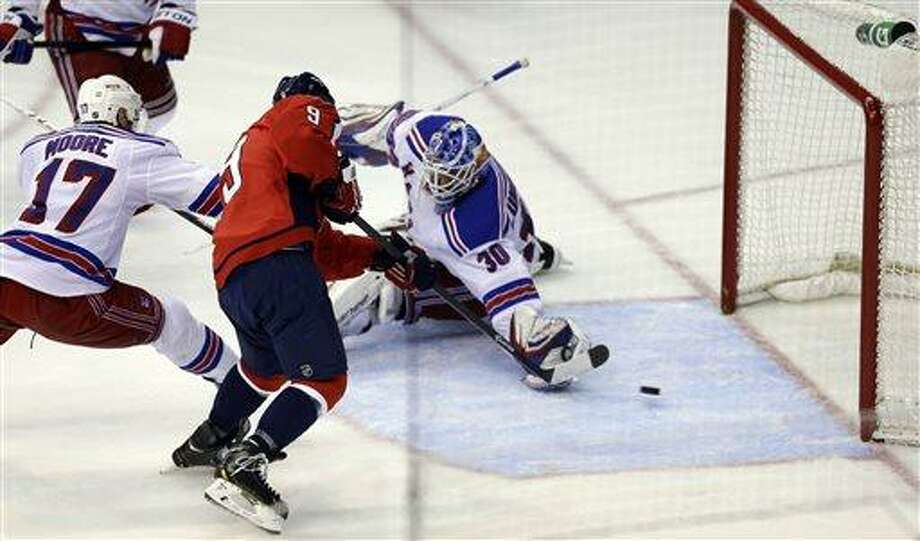 Washington Capitals center Mike Ribeiro (9) scores the game-winning goal past New York Rangers goalie Henrik Lundqvist (30), from Sweden, with defenseman John Moore (17) in overtime of Game 5 first-round NHL Stanley Cup playoff hockey series, Friday, May 10, 2013, in Washington. The Capitals won 2-1 in overtime. (AP Photo/Alex Brandon) Photo: AP / AP