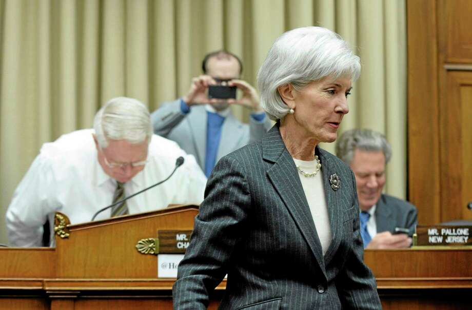 Health and Human Services Secretary Kathleen Sebelius walks to her seat to testify on Capitol Hill in Washington Dec. 11 before the House Energy and Commerce Committee hearing on the implementation failures of the Affordable Care Act. Sebelius went to shake the hands of Health subcommittee Chairman Rep. John Pitts, R-Pa., left, and ranking Democrat member Rep. Frank Pallone, D-N.J., right. Photo: Susan Walsh — The Associated Press   / AP