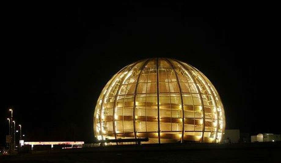 "FILE - In this March 30, 2010 file picture the globe of the European Organization for Nuclear Research, CERN, is illuminated outside Geneva, Switzerland. The world's largest and most powerful atom smasher goes into a 2-year hibernation in March 2013 , aiming to reach maximum energy levels that may lead to more stunning discoveries after hunting down the so-called ""God particle. But physicists at the European Center for Nuclear Research, known by its French acronym CERN, won't exactly be idle as the US $10 billion proton collider goes on hiatus for maintenance and retooling _ in preparation for unlocking more mysteries. There are still reams more data to sift through since the July 2012 discovery of a new subatomic particle called a Higgs boson and promises a new realm of understanding in subatomic science. (AP Photo/Anja Niedringhaus,File) Photo: ASSOCIATED PRESS / AP2010"