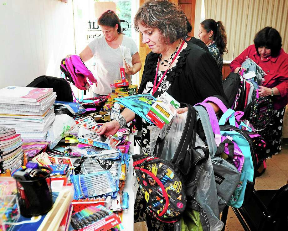 (Arnold Gold — New Haven Register)  Jennifer Olson, principal at Irving School in Derby, picks out donated school supplies for needy children at J Cuts Barber Shop in Shelton on 8/27/2013. Photo: Journal Register Co.