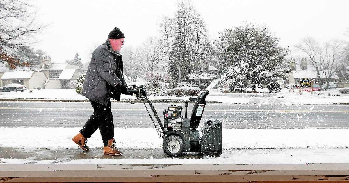 Dan Thewlis clears the sidewalk Dec. 10 in front of Island View Senior Housing in Milford.