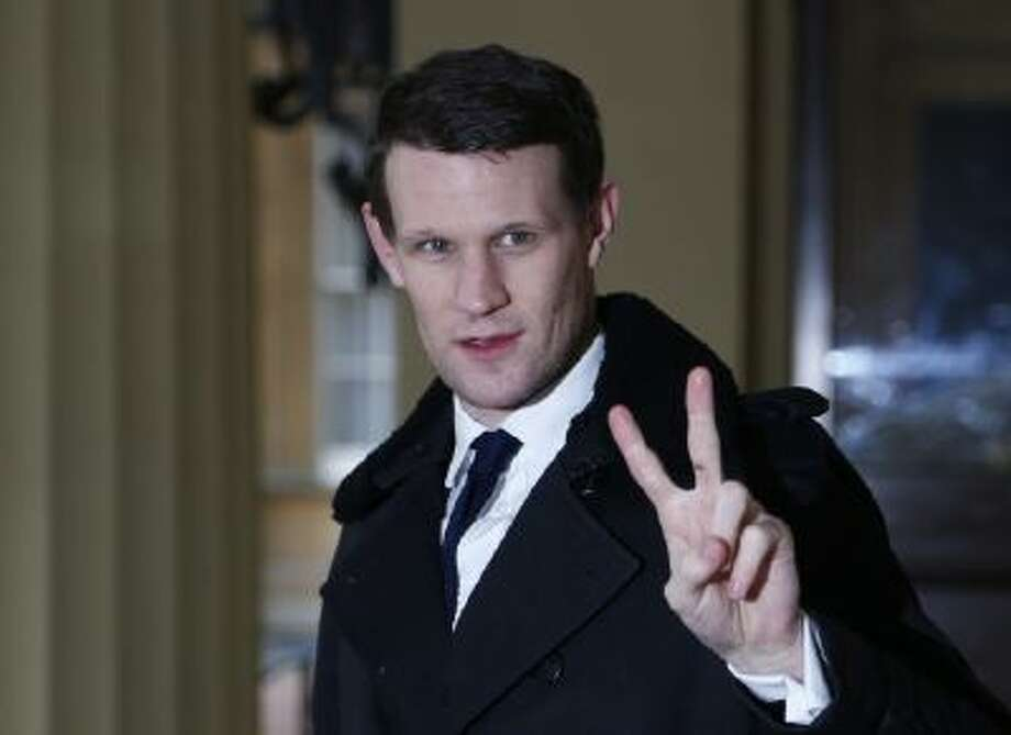 """In this Monday, Nov. 18, 2013 file photo British actor Matt Smith poses for the photographers as he arrives for a reception at Buckingham Palace, in central London. An energetic musical adaptation of Bret Easton Ellis' novel """"American Psycho,"""" about a soulless yuppie serial killer at large in 1980s Manhattan, has opened on stage in London, Dec. 2013. The show stars Matt Smith, best known as the galaxy-hopping hero of the BBC sci-fi series Doctor Who."""