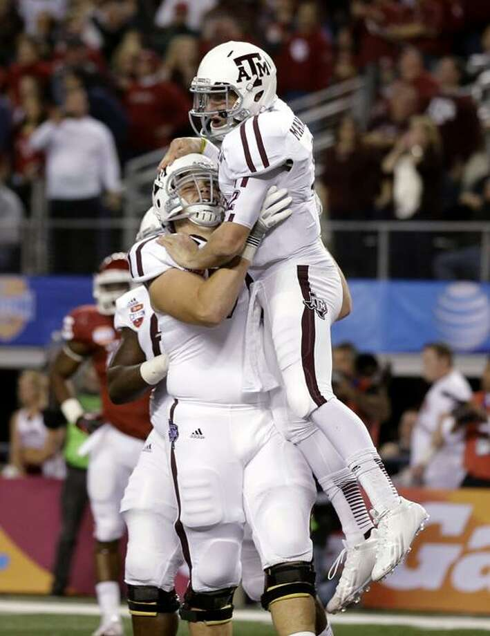 Texas A&M quarterback Johnny Manziel, right, celebrates his touchdown run with offensive linesman Luke Joeckel (76) in the first half of the Cotton Bowl NCAA college football game against Oklahoma on Friday, Jan. 4, 2013, in Arlington, Texas. (AP Photo/Tony Gutierrez) Photo: AP / AP