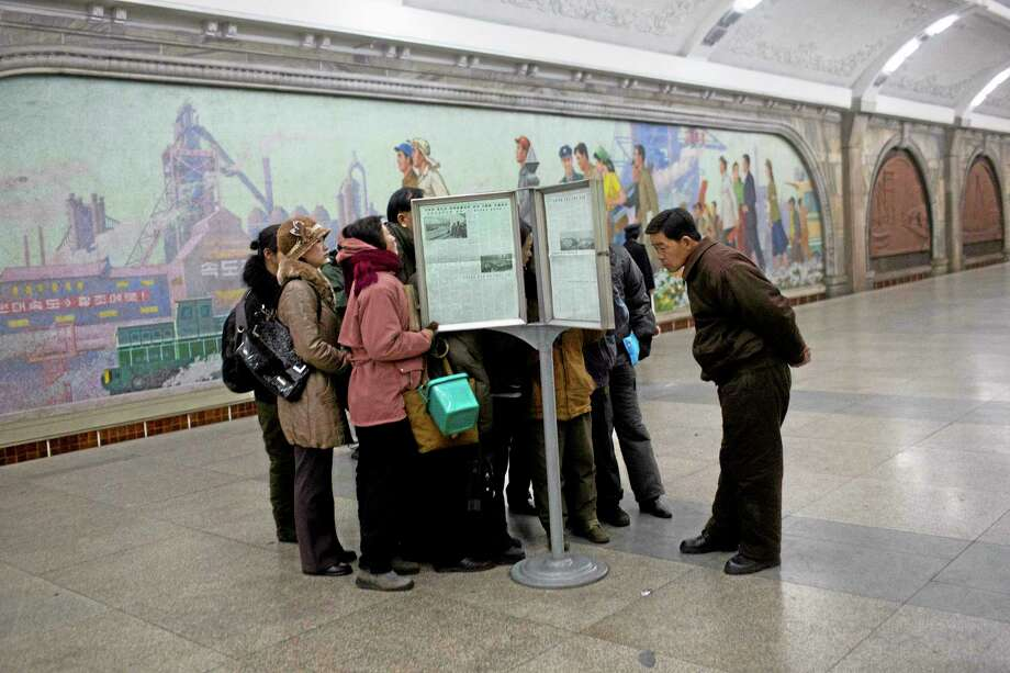 North Korean subway commuters gather around a public newspaper stand on the train platform in Pyongyang on Friday, Dec. 13, 2013 to read the headlines about Jang Song Thaek, North Korean leader Kim Jong Un's uncle who was executed as a traitor. (AP Photo/David Guttenfelder) Photo: AP / AP