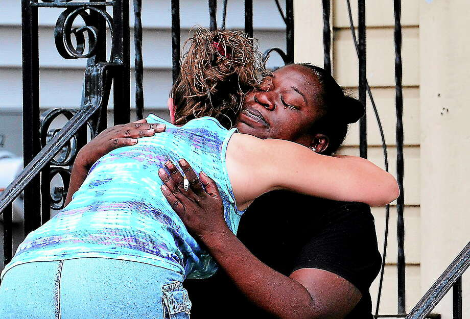 A relative of the shooting victim, right, is consoled by a neighbor outside 127 Clay St., the scene of an early morning shooting that left a city man dead. Photo: (Peter Casolino — New Haven Register)