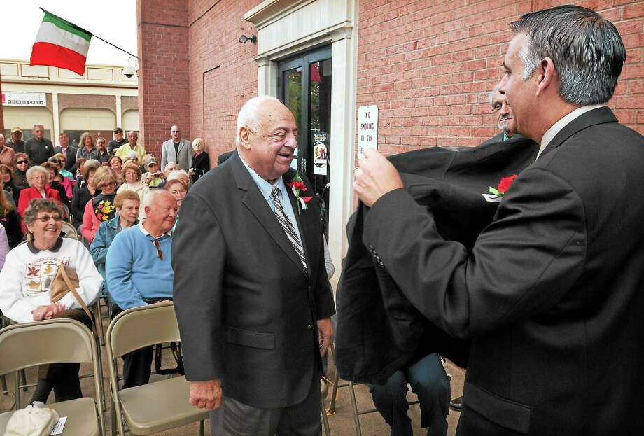 "West Haven Mayor John M. Picard presents Consorte with an embroidered jacket Friday after Consorte was named the city's ""Italian Person of the Year."" Photo: Mara Lavitt — New Haven Register   / Mara Lavitt"
