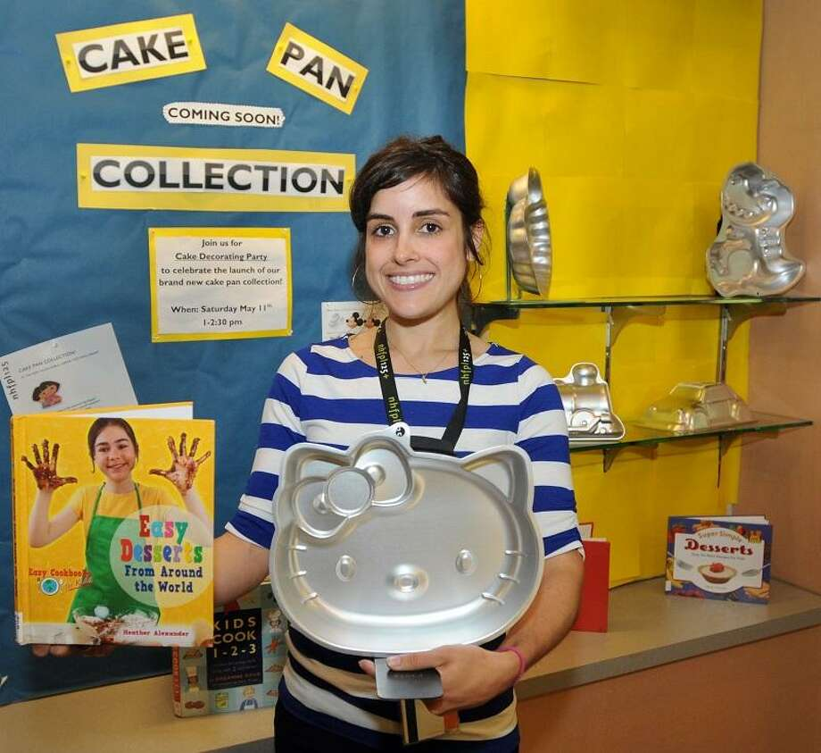 Sandra Hernandez, Young Minds Librarian of the New Haven Free Public Library, with a cake pan and a book on baking that people can check out of the library. The library has a new program to loan out cake pans the same way they check out books. Thursday May 9, 2013.  Photo by Peter Hvizdak / New Haven Register Photo: New Haven Register / ©Peter Hvizdak /  New Haven Register