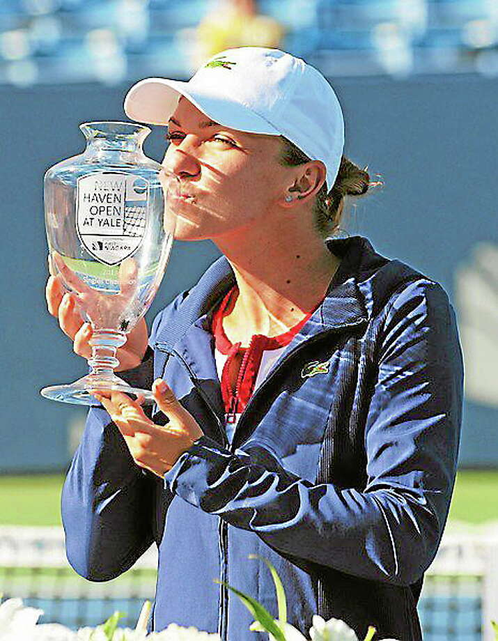 Simona Halep kisses the winner's trophy at the New Haven Open on Aug. 24 after defeating Petra Kvitova 6-2, 6-2. Photo: Bob Child — For The Register