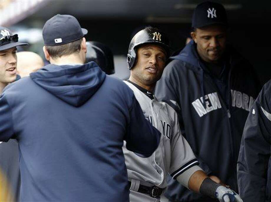 New York Yankees' Robinson Cano, center, is congratulated by teammates after hitting a solo home run against the Colorado Rockies in the fifth inning of a baseball game in Denver, Thursday, May 9, 2013. (AP Photo/David Zalubowski) Photo: AP / AP