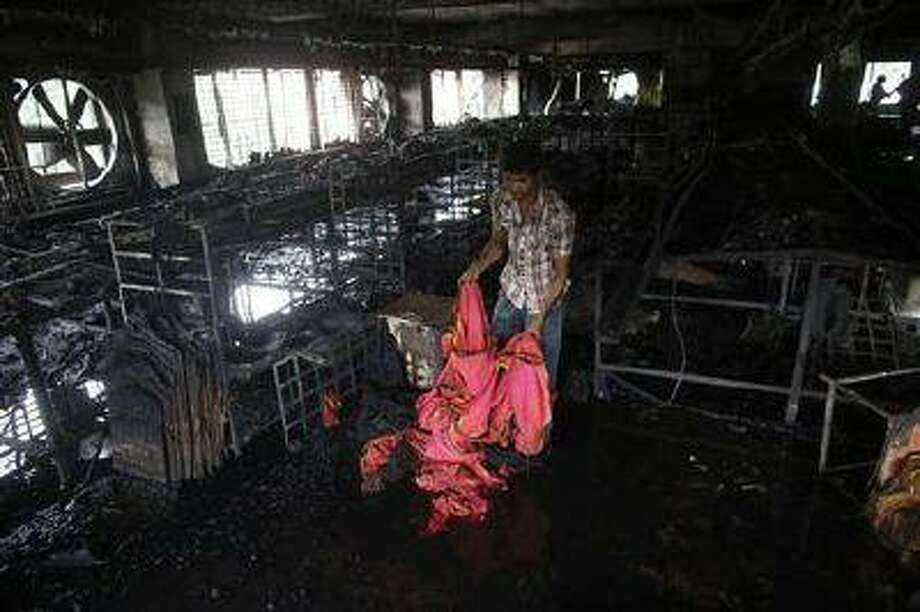 A garment worker inspects a factory belonging to Tung Hai Group, a large garment exporter, after a fire in Dhaka May 9.