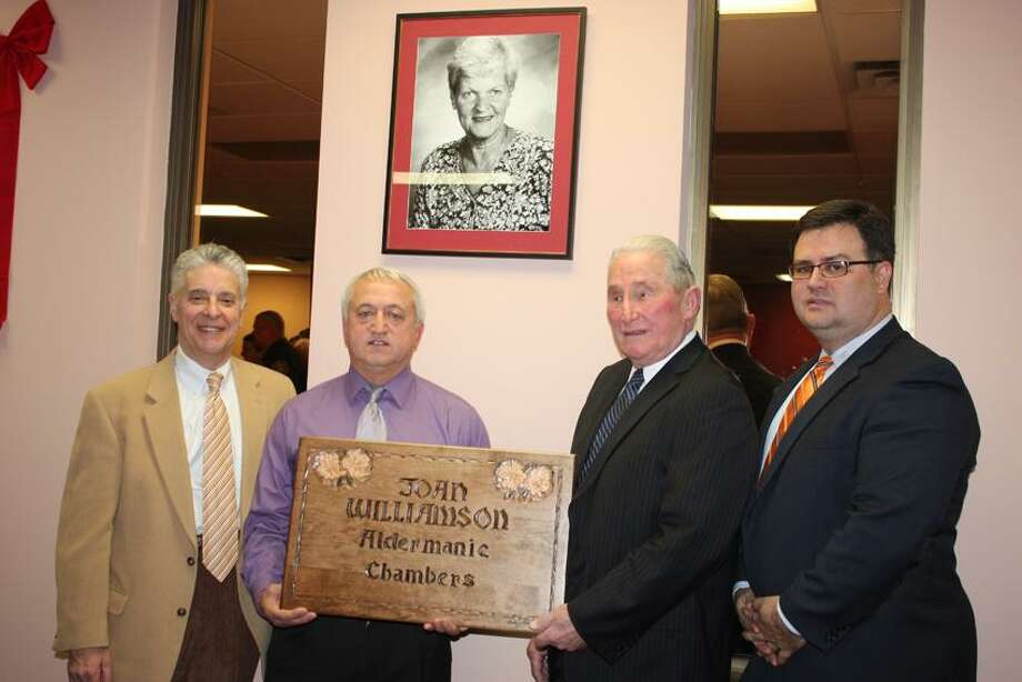From left, Attorney Jamie Cohen, Mayor Anthony Staffieri, Bernard Williamson and City Treasurer Keith McLiverty with hand-carved sign that will grace the new Joan Williamson Aldermanic Chambers in City Hall.
