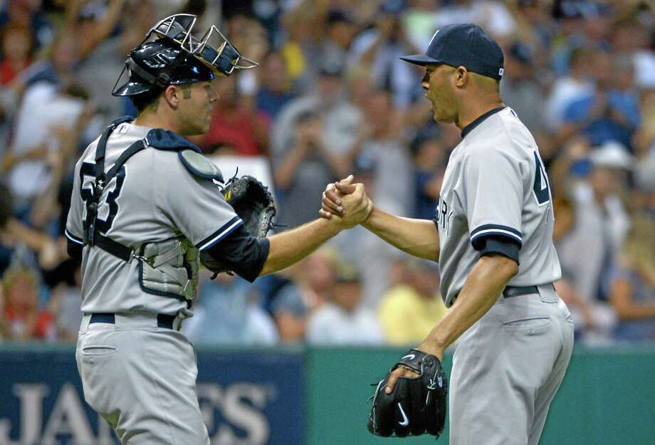 Yankees reliever Mariano Rivera, right, is congratulated by catcher Austin Romine after getting the save in a 3-2 victory over the Tampa Bay Rays Sunday. Photo: Phelan M. Ebenhack — The Associated Press   / FR121174 AP