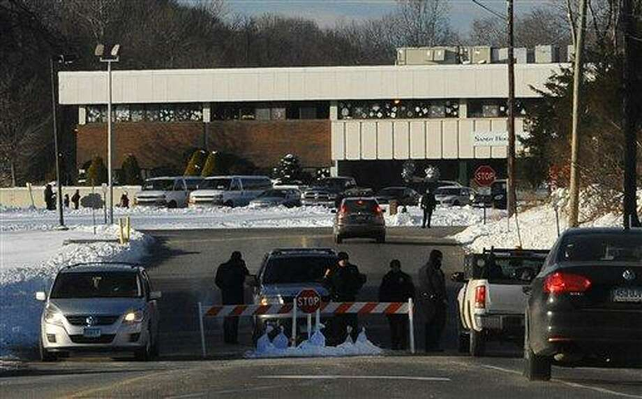 A police road block is at the entrance to the new Sandy Hook Elementary School on the first day of classes in Monroe, Conn., Thursday, Jan. 3, 2013. The school, formerly known as Chalk Hill School, was overhauled specially for the students from the Sandy Hook School shooting in Newtown, in the neighboring town of Monroe, Conn. (AP Photo/Jessica Hill) Photo: AP / FR125654 AP
