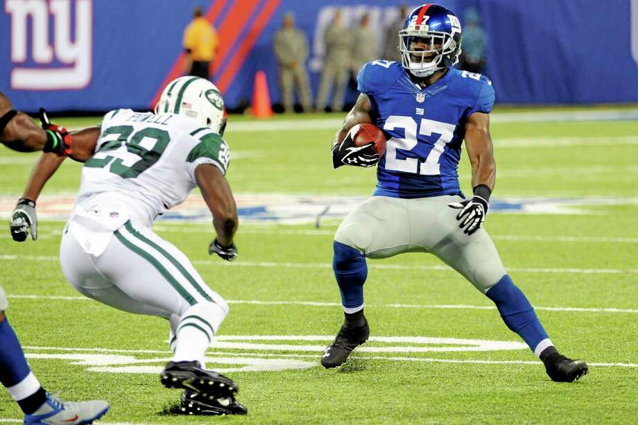 Giants safety Stevie Brown (27) runs back an interception during the first half of a preseason game as New York Jets running back Bilal Powell (29) attempts to tackle him on Saturday. Photo: Bill Kostroun — The Associated Press   / FR51951 AP