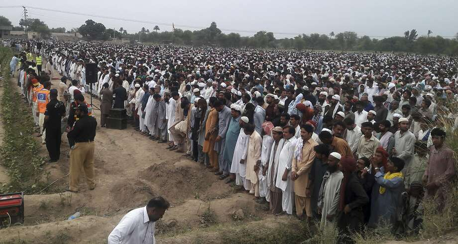 People offer prayers for the victims of the fuel tanker fire in Bahawalpur. Thousands of mourners in Pakistan attended the collective funeral. Photo: Iram Asim, Associated Press