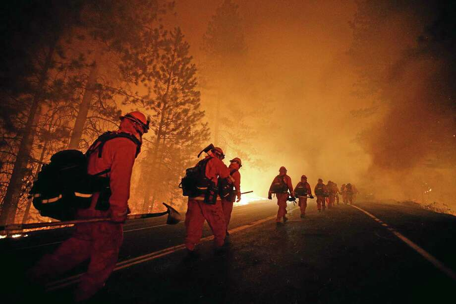 Inmate firefighters walk along Highway 120 after a burnout operation as firefighters continue to battle the Rim Fire near Yosemite National Park, Calif., on Sunday, Aug. 25, 2013. Fire crews are clearing brush and setting sprinklers to protect two groves of giant sequoias as a massive week-old wildfire rages along the remote northwest edge of Yosemite National Park. (AP Photo/Jae C. Hong) Photo: AP / AP