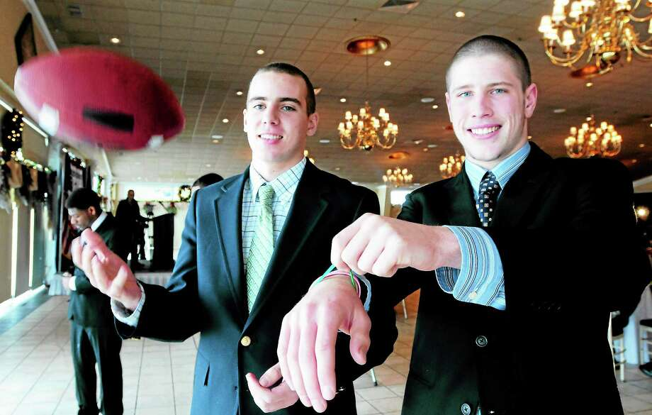 Stephen Walsh, left, and Colton Smith of Fairfield Prep, both of Newtown, are seen at the CIAC Football Finals Luncheon at the Aqua Turf in Plantsville Thursday as Smith shows of his green Newtown wristband. Photo: Peter Hvizdak — New Haven Register       / ©Peter Hvizdak /  New Haven Register