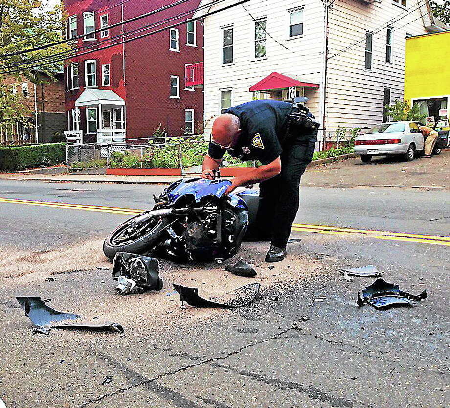 Officer Armando Vale surveys a motorcycle after it crashed into the back of a school bus Thursday in New Haven. Photo: Rich Scinto — New Haven Register