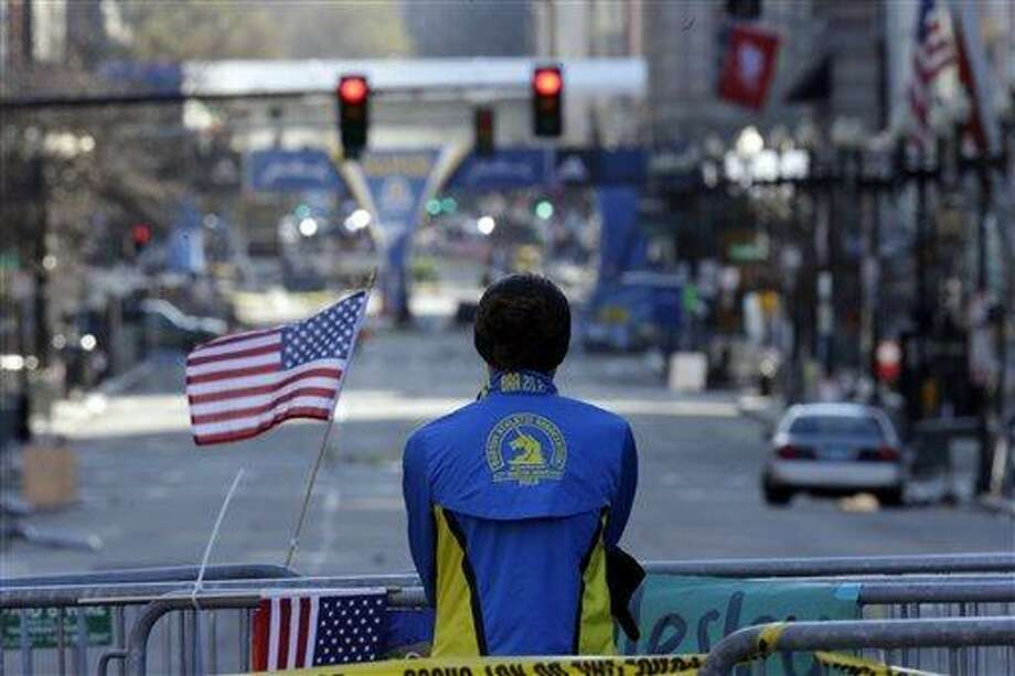 Lizzie Lee of Lynnwood, Wash., pauses near the finish line of Monday's Boston Marathon explosions, which killed at least three and injured more than 140, Thursday, April 18, 2013, in Boston. Lee said she almost completed the marathon before the blasts. (AP Photo/Matt Rourke) Photo: AP / 2013 AP