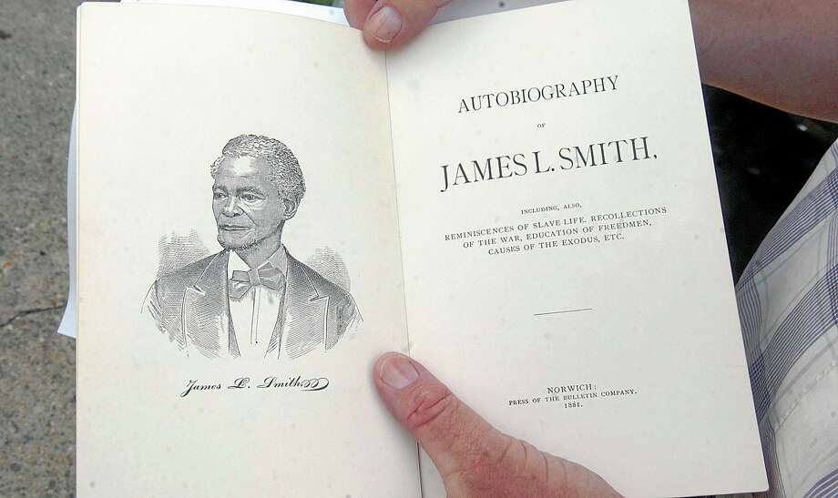 In this July 24, 2013 photo, historian Dale Plummer holds the autobiography of escaped slave James L. Smith, who bought a home at 59 School Street in Norwich, Conn., in 1848. The city recently acquired the house where Smith lived in freedom and remarkable prosperity. (AP Photo/Norwich Bulletin, John Shishmanian) Photo: AP / Norwich Bulletin