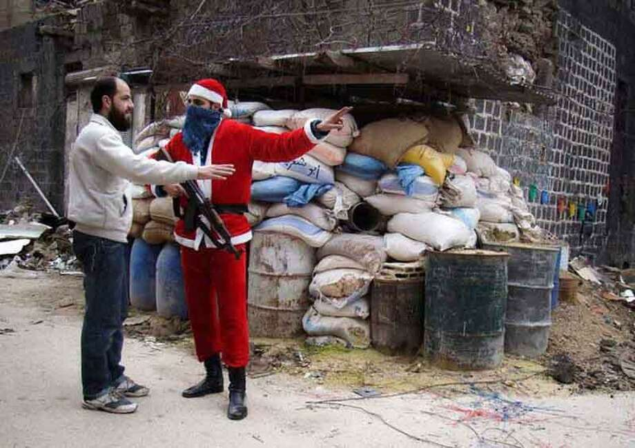 In this picture taken on Tuesday, Jan. 1, 2013, a citizen journalism image provided by Lens Young Homsi, which has been authenticated based on its contents and other AP reporting, a Free Syrian Army fighter wears as a Santa Claus suit and holds his AK-47, right, as he directs a civilian man, in the old city of Homs, Syria. (AP Photo/Lens Young Homsi) Photo: ASSOCIATED PRESS / AP2013