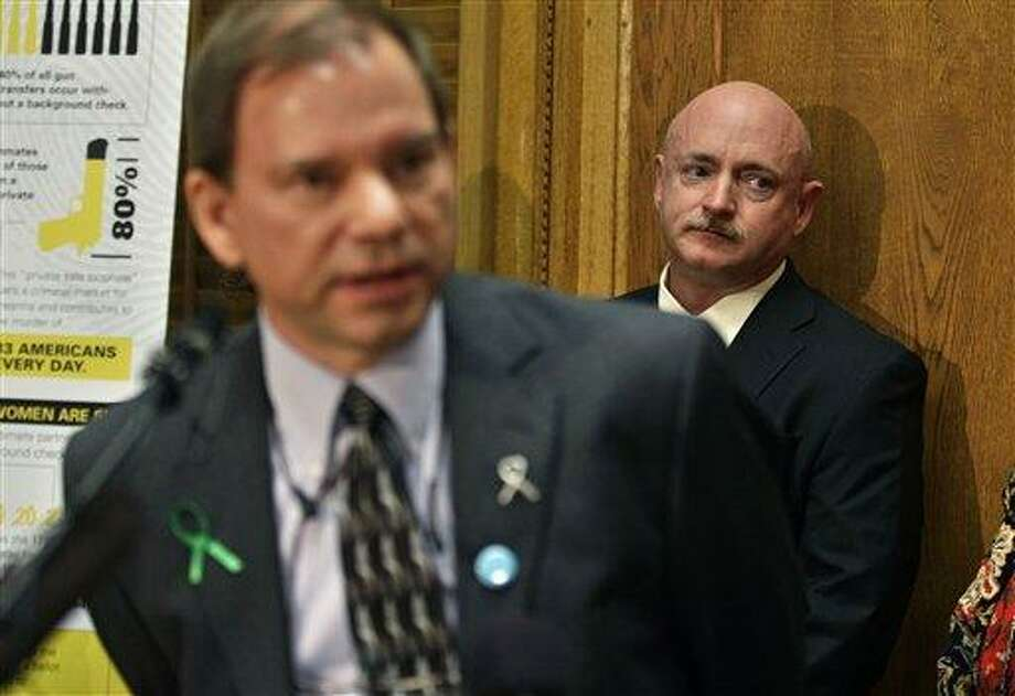 Mark Kelly, husband of former U.S. Rep. Gabrielle Giffords,  listens to Tom Mauser, the father of Columbine High School shooting victim Daniel Mauser, speak during a news conference in favor of proposed gun control legislation at the State Capitol, in Denver, Monday March 4, 2013. State Senate committees began work Monday on a package of gun-control measures that already have cleared the House which include limits on ammunition magazine sizes and expanded background checks to include private sales and online purchases. (AP Photo/Brennan Linsley) Photo: AP / AP