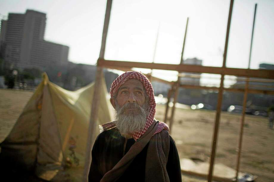 An Egyptian man stands in front of his tent in Tahrir Square where a few protesters have built their camp protesting against the release of Egypt's ousted President Hosni Mubarak in Cairo, Egypt, Saturday, Aug. 24, 2013. (AP Photo/Manu Brabo) Photo: AP / AP