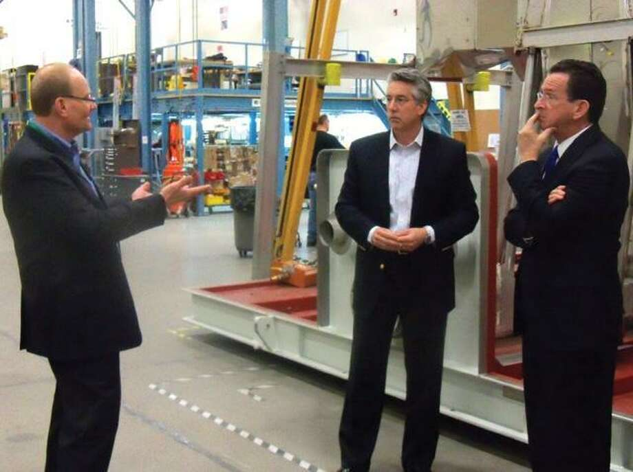 FuelCell Energy Vice President of Government Business Frank Wolak explains the finalization of the fuel cell process, along with CEO Chip Bottone, to Gov. Dannel P. Malloy during his visit to the plant on Wednesday. File photo.