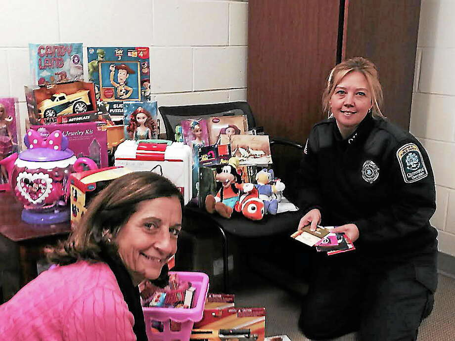 From left, Pat Polvani, secretary to the chief of public safety, and Shanon Grasso, public safety officer, with some of the toys they have collected in lieu of parking tickets. Contributed photo Photo: Journal Register Co.