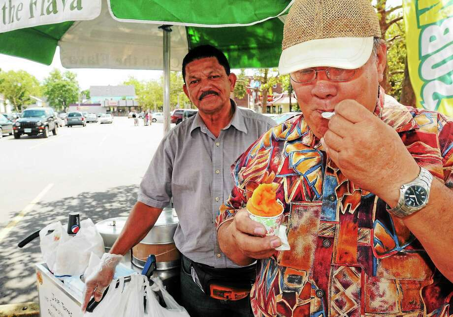 Mara Lavitt — Register August 14, 2013 New Haven. Jose Torres has owned the Delicioso Coco Helado ice cream cart for 14 years. He can often be found at the corner of Ferry St. and Grand Ave. Regular customer Cecilio Gonzalez of New Haven savors the mango. Photo: Journal Register Co.