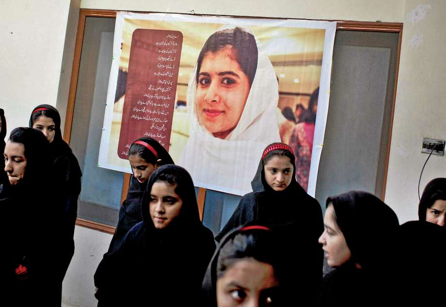In this Thursday, Nov. 15, 2012 photo, Pakistani girls gather under a poster of Malala Yousufzai in her old school in Mingora, Swat Valley, Pakistan. The giant poster of her that once emblazoned the wall of the assembly hall has been removed. The school made no plans to recognize the anniversary of Malala's shooting by Taliban, teachers and students are afraid.  (AP Photo/Anja Niedringhaus) Photo: AP / AP