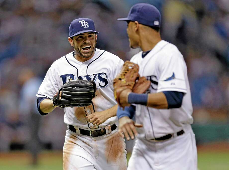 Tampa Bay Rays left fielder David DeJesus, left, celebrates with teammate center fielder Desmond Jennings after robbing New York Yankees' Chris Stewart of an extra-base hitduring the seventh inning of a baseball game Friday, Aug. 23, 2013, in St. Petersburg, Fla. (AP Photo/Chris O'Meara) Photo: AP / AP