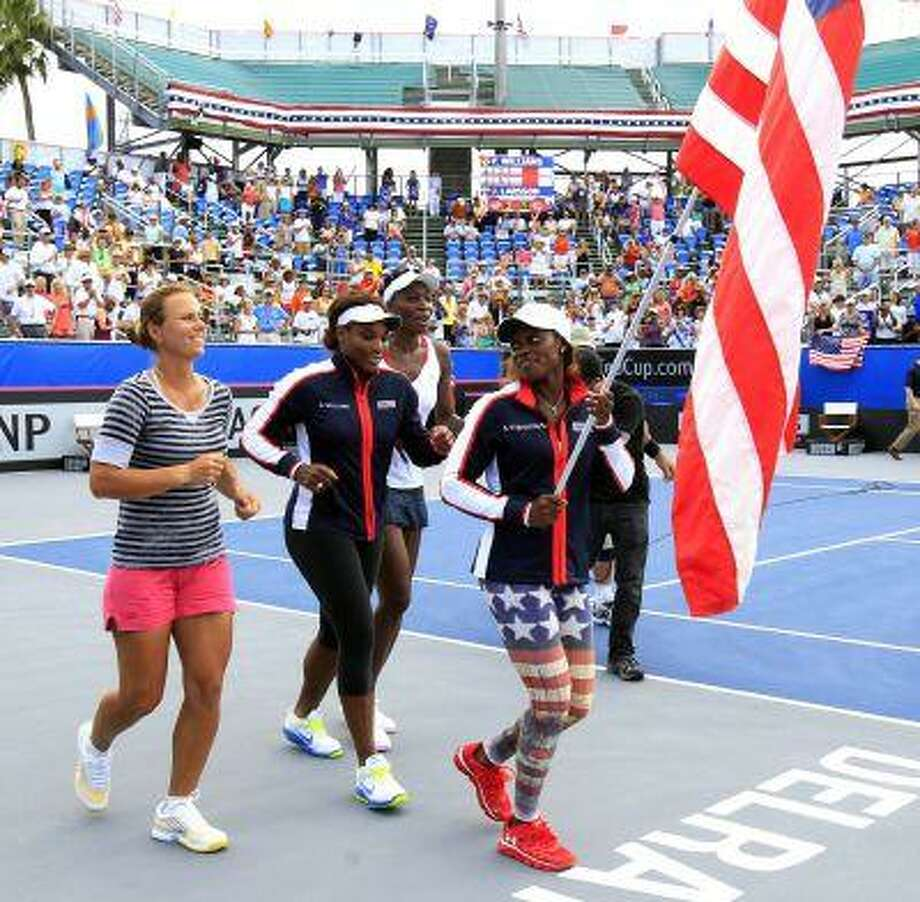 From left, United States team members Varvara Lepchenko, Serena Williams, Venus Williams and Sloane Stephens celebrate their victory over Sweden following a Fed Cup World Group tennis match, Sunday, April 21, 2013, in Delray Beach, Fla. (AP Photo/Palm Beach Post, Richard Graulich) MAGS OUT; TV OUT; NO SALES Photo: ASSOCIATED PRESS / AP2013