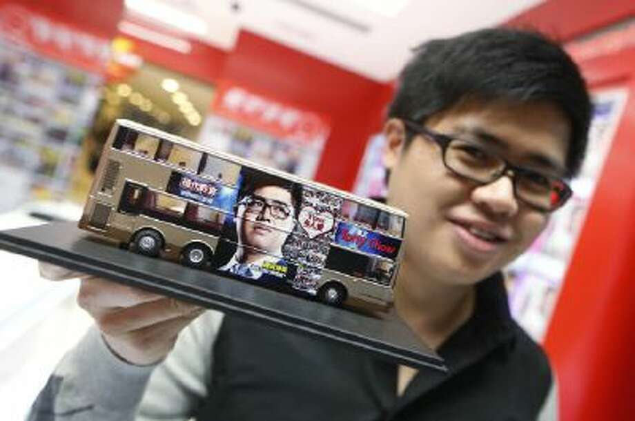 English grammar tutor Tony Chow, shows his advertising plan with a model of a double decker bus with his face plastered on the sides.