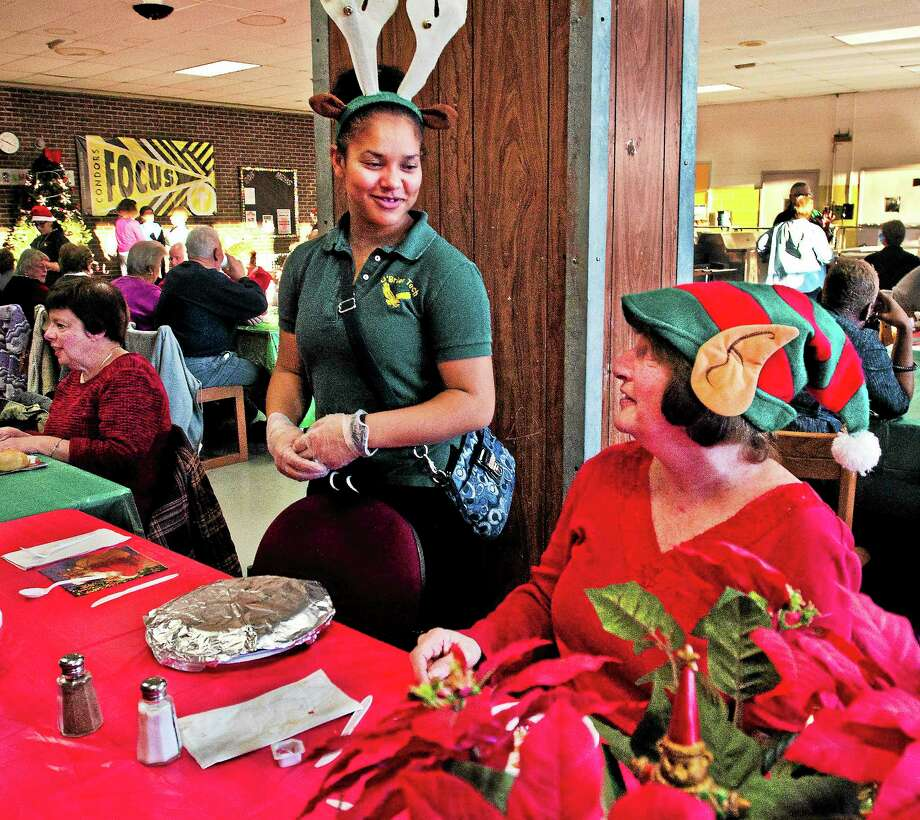 (Melanie Stengel ó New Haven Register  Emmet O'Brien junior, Giya Perrin (L)  chats with diner, Claudia Degnan during the annual Christmas dinner that students host for the community 12/12. Photo: Journal Register Co.