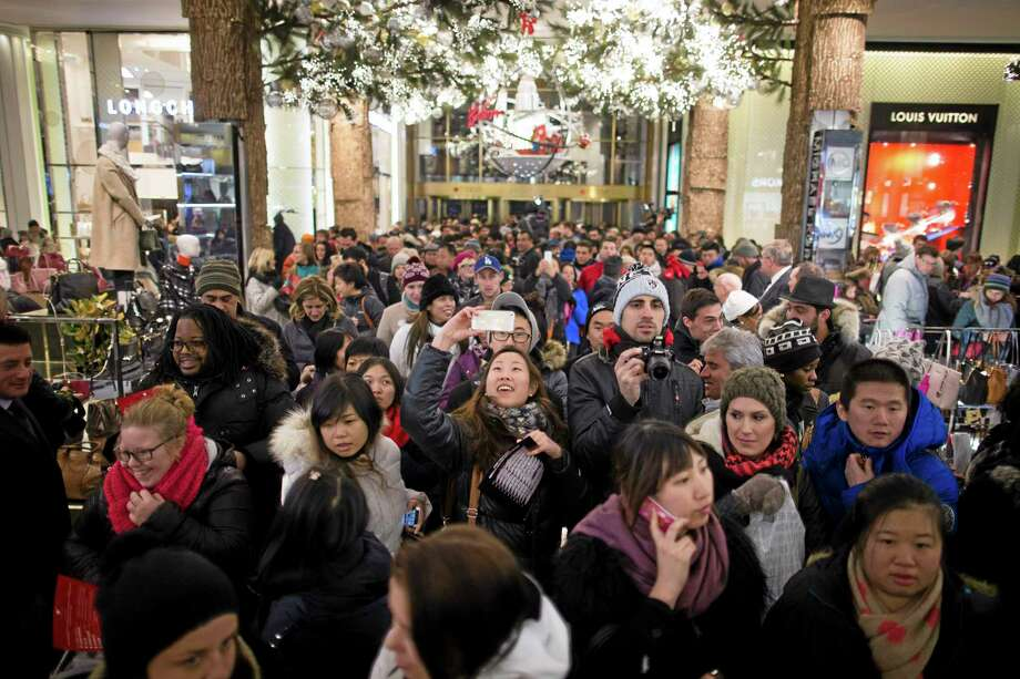 FILE - In this Thursday, Nov. 28, 2013, photo, a shopper takes a selfie as crowds pour into the Macy's Herald Square flagship store in New York. The government reports on sales at U.S. retailers in November on Thursday, Dec. 12, 2013. (AP Photo/John Minchillo) Photo: AP / FR170537 AP