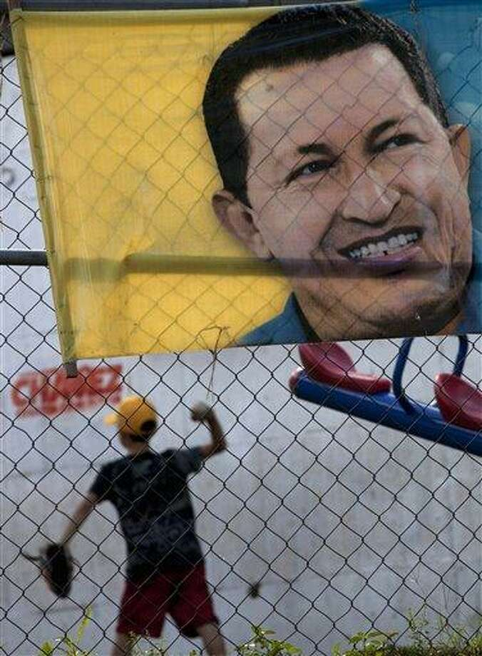 A boy plays behind a poster with an image depicting Venezuela's President Hugo Chavez in Caracas, Venezuela, Thursday, Jan. 3, 2013. The ailing president's health crisis has raised contentious questions ahead of the swearing-in set for Jan. 10, including whether the inauguration could legally be postponed. Officials have raised the possibility that Chavez might not be well enough to take the oath of office, without saying what will happen if he can't. The constitution says that if a president or president-elect dies or is declared unable to continue in office, presidential powers should be held temporarily by the president of the National Assembly and that a new presidential vote should be held within 30 days. (AP Photo/Ariana Cubillos) Photo: AP / AP