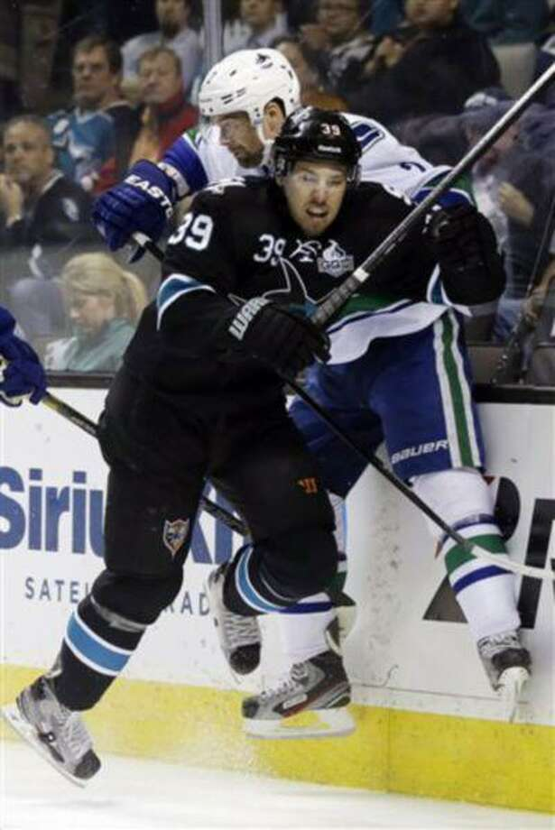 San Jose Sharks center Logan Couture (39) collides against the boards with Vancouver Canucks defenseman Dan Hamhuis during the first period of Game 4 of their first-round NHL hockey Stanley Cup playoff series in San Jose, Calif., May 7, 2013. Photo: AP / AP