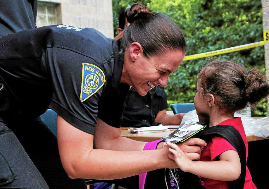 Officer Liz Wright puts a backpack on 3-year-old Elliana Lugo. Police in Westville collected an estimated 300 backpacks and school supplies for kids in the area. Photo by Rich Scinto/ New Haven Register. Photo: Journal Register Co.