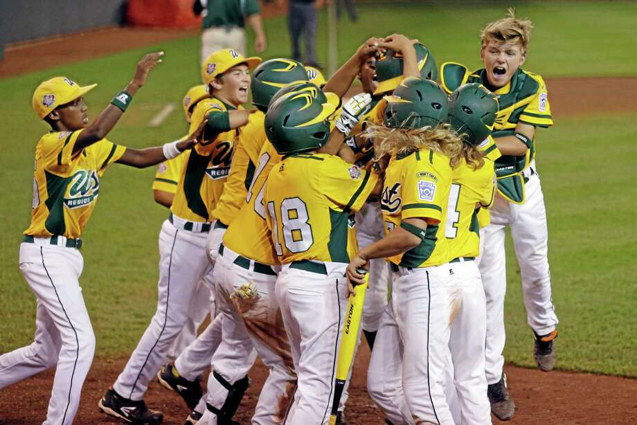 Chula VIsta, Calif.'s Grant Holman is swarmed by celebrating teammates after hitting a three-run home run off Westport, Conn., pitcher Max Popken in the ninth inning of a baseball game at the Little League World Series in South Williamsport, Pa., Wednesday, Aug. 21, 2013. Chula Vista won 6-3. (AP Photo/Gene J. Puskar) Photo: AP / AP