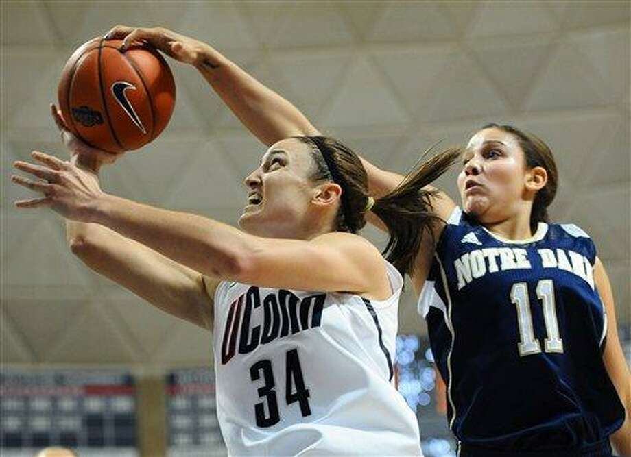 Notre Dame's Natalie Achonwa, right, blocks a shot by Connecticut's Kelly Faris during the first half of an NCAA college basketball game in Storrs, Conn., Saturday, Jan. 5, 2013. Notre Dame beat No. 1 UConn 73-72. (AP Photo/Jessica Hill) Photo: ASSOCIATED PRESS / A2013