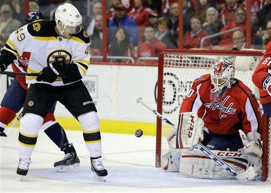 Boston Bruins center Rich Peverley (49) tries to get around to the puck deflected by Washington Capitals goalie Braden Holtby (70) in the second period of an NHL hockey game, Tuesday, March 5, 2013, in Washington. (AP Photo/Alex Brandon) Photo: ASSOCIATED PRESS / AP2013
