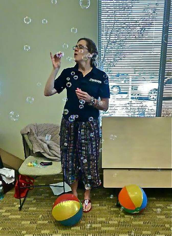 Instructor Maureen Helgren blows bubbles at the beginning of Friday's Healthy Steps class at the Center for Cancer Care at Griffin Hospital in Derby. Patricia Villers/Register