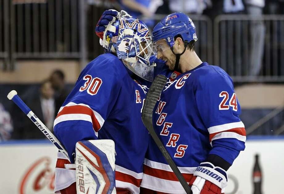 New York Rangers right wing Ryan Callahan (24) celebrates with goalie Henrik Lundqvist (30), of Sweden, after their 4-3 win over the Washington Capitals at the end of Game 4 of their first-round NHL hockey Stanley Cup playoff series in New York, Wednesday, May 8, 2013. (AP Photo/Kathy Willens) Photo: AP / AP
