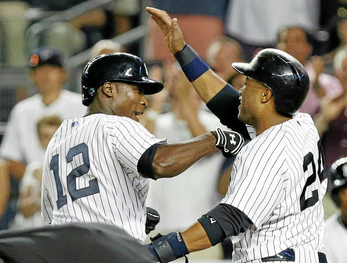 New York Yankees' Alfonso Soriano (12) and Robinson Cano celebrate after Soriano's two-run home run during the eighth inning of a baseball game against the Toronto Blue Jays on Wednesday, Aug. 21, 2013, in New York. The Yankees won 4-2. (AP Photo/Frank Franklin II)